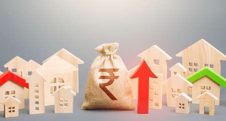 Indian rupee money bag and a city of house figures and red up arrow. Recovery and growth in property prices, high demand. Investments. Increase in revenues to municipal budget. Rent growth. Stock Photo