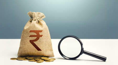 Indian rupee money bag and magnifying glass. Financial audit and monitoring of suspicious capital and transactions. Search for business beneficiaries. Budget check. Attracting investments financing. Stock Photo
