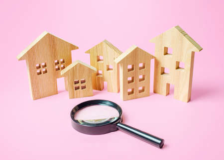 Many wooden figures of houses and a magnifying glass. Search for housing to buy or rent, realtor services. Find the best real estate option. Criteria and advice for making the right choice.