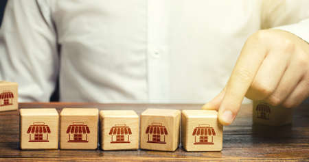Man puts blocks with shop symbols in a row. Building a successful business empire. Franchise concept. Merging competitor, creation of a large network monopoly. Commercial association