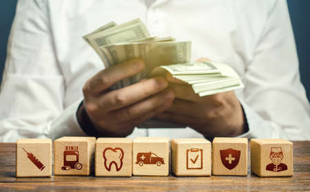 A man counts money over blocks with medical attributes symbols. High medical expenses and service bills. No medicinal insurance. Big cost and availability of medicine. Increasing healthcare funding.