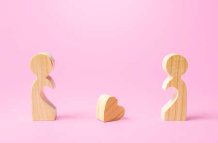 Figurines of people separated from each other and a lost heart. Breakup, end of love. Relationship problems of the couple. Take the first step towards reconciliation. Not whole without each other