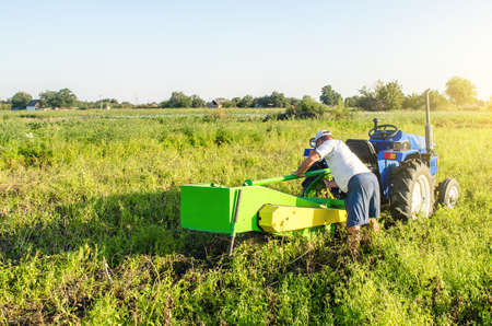 A farmer serves a tractor on a farm plantation field. Repair of the potato digging machine. Maintenance of equipment and machines. Unexpected breakdown during harvesting work. Tractor service. Editorial