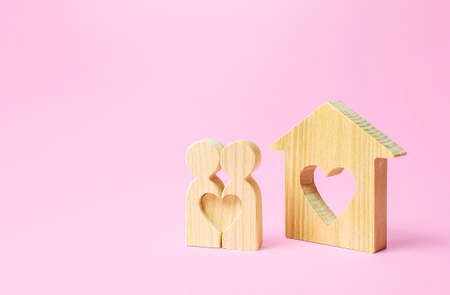 Figures of a love couple stand near house with a heart. Affordable cheap housing for young couples and newlyweds. Stimulating of appearance of new families, preferential mortgage loans, social support