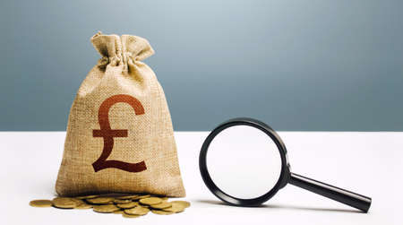 British pound sterling money bag and magnifying glass. Financial audit and monitoring of suspicious capital and transactions. Budget check. Attracting investments financing. Search for beneficiaries.