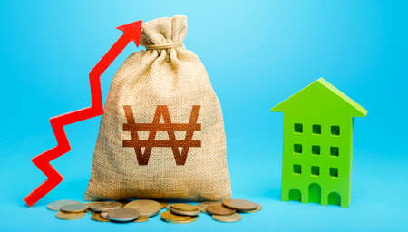 South korean won money bag with red up arrow and residential building. Return on investment. Increase in prices for apartments and housing. Recovery and growth in property cost. Municipal budget.