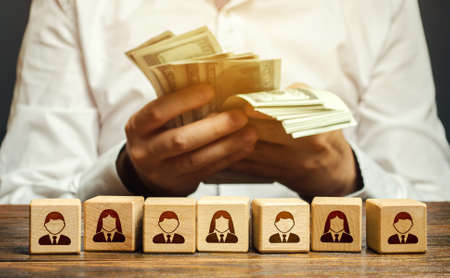 A man is counting money in his hands over blocks with symbols of employees. Wage fund. Accounting and budgeting. Payday. Expanding a profitable business, recruiting and training employees.