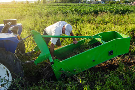 A farmer examines a machine for digging out potato root vegetables. Exploitation and maintenance of equipment. Farming agriculture and farmland. Harvesting potatoes in autumn.