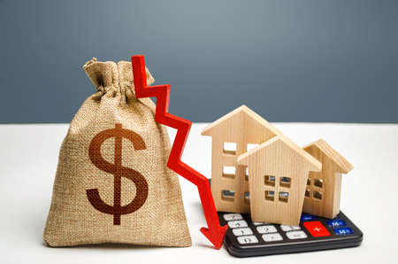 Dollar money bag with down arrow and houses on calculator. Falling real estate market, low prices and demand. Saving resources and reducing maintaining cost, increasing energy efficiency, technology.