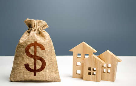 Dollar money bag and figurines of residential buildings. Mortgage loan. City municipal budget. Investment in real estate. Costs of service and maintaining buildings. Purchase of housing. Property tax Stock Photo