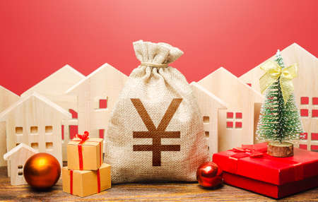 Yuan Yen money bag and houses in a New Year's setting. Increase in investment attractiveness, prosperity. Promotions, offers. New Year or Xmas winter holiday. Mortgage loans. Bank deposit, credit.