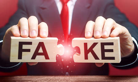 A man breaks a fake puzzle. Exposing fake news and false info. Debunking myths. Investigation of doubtful facts, information hygiene. Timely refutation. Stop influencing public opinion Stok Fotoğraf