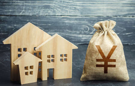 Yuan Yen money bag and figurines of residential buildings. Financing urban development and infrastructure projects. Property tax. Municipal budgeting. Increase in investment attractiveness, prosperity. Stock fotó