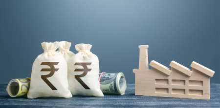 Indian rupee money bags and industrial factory plant. Investments in production and energy industry. Concession auction tender. Budget-forming subjects of economy. Subsidies and support for businesses