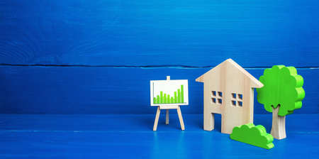 Residential building and easel with green positive upward trend chart. Recovery of the real estate market, growing prices and demand for housing. Growth and development, investment. Energy efficiency Stock fotó