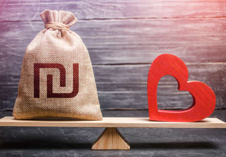 Israeli shekel money bag and red heart on scales. Funding healthcare. Health life insurance financing concept. Support and life quality improvement. Reforming and preparing for new challenges. Stockfoto - 159020456