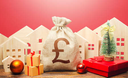 British pound sterling money bag and houses in a New Year's setting. New Year or Xmas winter holiday. Increase in investment attractiveness. Promotions, offers. Mortgage loans. Bank deposit