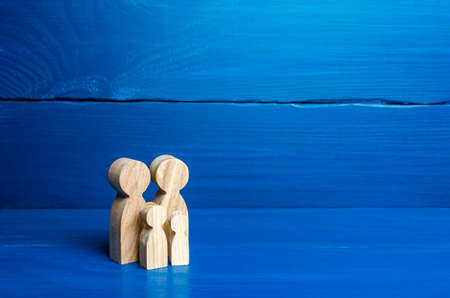 Family figures of parents and kids on a blue background. Family values and health. Adoption and custody of children. Social support, demography, sociology. Upbringing and education. Together concept Stockfoto - 159020466