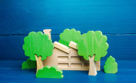 Industrial factory plant hidden behind the trees. Greenwashing concept. PR and trend about caring for environment. Misleading customers and buyers of products and maximizing profits. Hiding facts Фото со стока