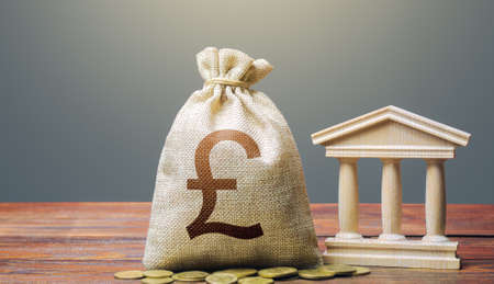 British pound sterling money bag and bank / government building. Tax collection and budgeting. Monetary policy. Support businesses in times of crisis. Lending loans, deposits. State debt. GDP and GNP.