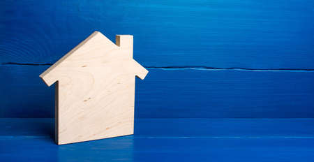 Wooden plane in shape of house figurine on a blue background. Minimalism. Real estate concept. Buying and selling. Housing, realtor services. Construction industry, building maintenance. Mortgage loan Stockfoto