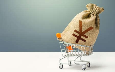 Yuan Yen money bag in a shopping cart. Profits and super profits. Minimum living wage. Business and trade concept. Public budgeting. Economic bubbles. Loans, microloans. Consumer basket. Фото со стока