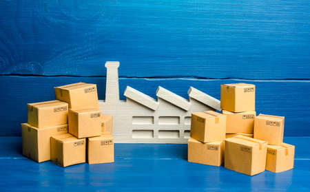 A figurine of a plant and a lot of boxes. The concept of overproduction of goods. Overstocking of manufacturer's warehouses, low demand and problems in transport logistics. Economic crisis slowdown