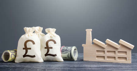 British pound sterling money bags and industrial factory. Investments in production and energy industry. Subsidies support for businesses. Concession auction tender. Budget forming economy subjects Stock Photo