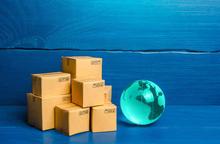Planet Earth globe and boxes. Global business and world trade. Distribution of goods, import and export of products. Freight shipping delivery to new markets. International trade and transportation. Banco de Imagens