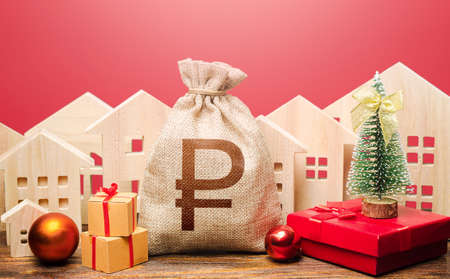 Russian ruble money bag and houses in a New Year's setting. Bank deposit. Promotions, offers. New Year or Xmas winter holiday. Increase in investment attractiveness. Mortgage loans. Stock fotó