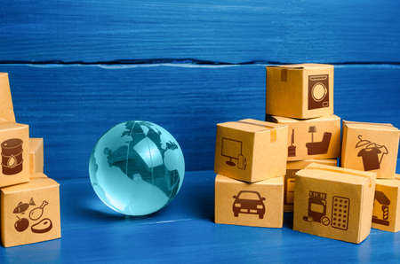 Planet Earth globe and cardboard boxes mass consumption products.