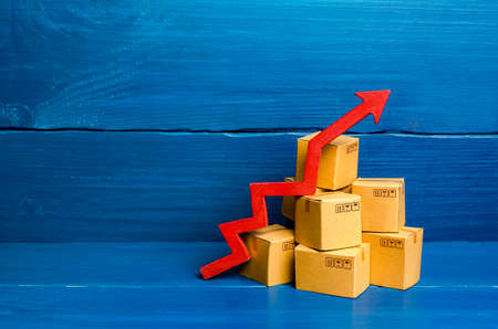 Cardboard boxes and red arrow up. Transformation of the economy and trade into online marketplaces, the growth of e-commerce and online shopping. Growing business activity. Rise in price of goods.