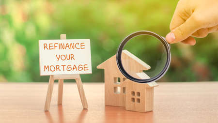 Inscription Refinance your mortgage and miniature houses. Real estate, finance and business concept. Interest rates. Property financing concept