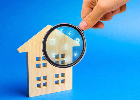 Realtor examines houses through a magnifying glass. Review of the real estate market, search for the best offers based on the criteria of price, location, area, infrastructure. Customer preferences. 免版税图像