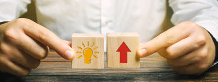 A businessman is holding wooden blocks depicting a business idea and up arrow. Concept of new innovation ideas and discoveries. Vision, planning. Strategy and management
