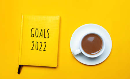 Notebook with the words Goals 2022 and a cup of coffee on a yellow background. Motivation, inspiration. Planning, plans and tasks. New business ideas. Setting goal, target.