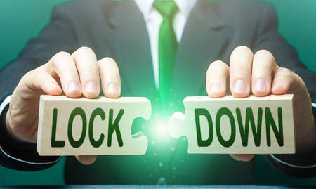A man breaks apart puzzles with the word Lockdown. The end of the period of strict quarantine measures. Resumption of the work of commerce and trade. Support economy. New normal. Easing prohibitions Stockfoto