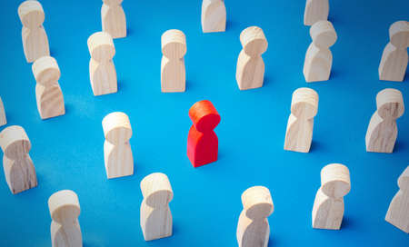 Red man figurine in a people crowd. Stands out from the crowd. Different, special. Collective immunity. Social distance. Intruder detection. A talented and capable candidate. Tolerance in society