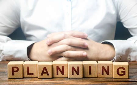 Man folded his hands on a background of blocks with the word Planning. Leadership quality to plan the best options for further action. Provide for any possible consequences. Discretion, determination