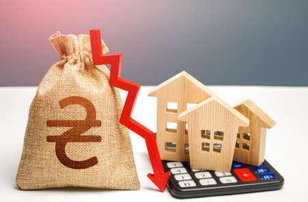Ukrainian hryvnia money bag with down arrow and houses on calculator. Falling real estate market, low prices and demand. Reducing maintaining cost, increasing energy efficiency. Saving resources. Archivio Fotografico - 166689144