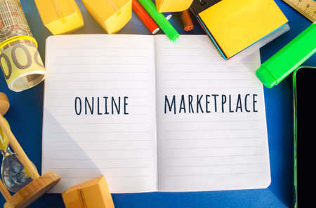 Notebook with the inscription Online marketplace. E-commerce website. Online store that allows other sellers to sell their goods for a certain fee. Boxes, hourglass, money. Flat lay