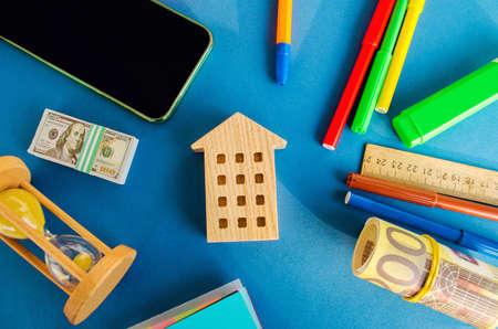 Miniature wooden house, money and hourglass on a blue background. Real estate concept. Affordable housing. Apartments for rent. Buying a house. Credit, loan, mortgage. Investments Archivio Fotografico