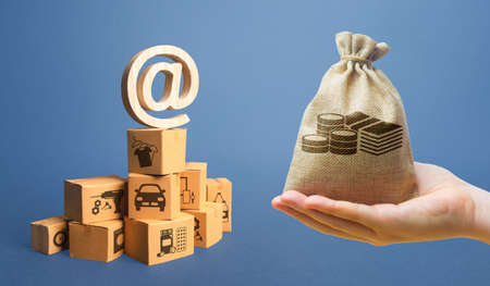 Money bag, stack of boxes and email internet symbol. Online Internet distribution of goods. E-commerce. Network marketing advertising. Remote non-contact trade services. Economic reorientation Archivio Fotografico