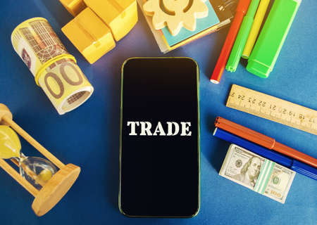 Phone with the word Trade on a blue background with money, boxes and hourglass. Business market and finance concept. Transfer of goods or services. Money, economy. Business deal. Trading Archivio Fotografico - 167072137