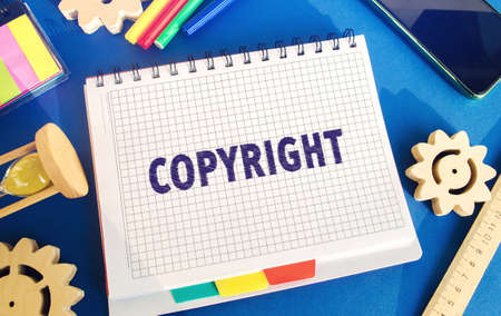 Notebook with the word Copyright. Patenting. Copyright protection. Brand and patent. The fight against online piracy. Gears, hourglass. Blue background Archivio Fotografico
