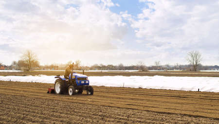 Farmer on a tractor with milling machine loosens, grinds and mixes soil. Loosening the surface, cultivating the land for further planting. Farming and agriculture. Cultivates the soil. Plows a field. Archivio Fotografico - 166940582