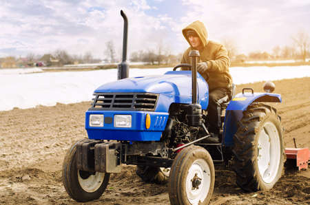 Farmer on a tractor with milling machine loosens, grinds and mixes soil. Loosening the surface, cultivating the land for further planting. Farming and agriculture. Cultivates the soil. Plows a field.