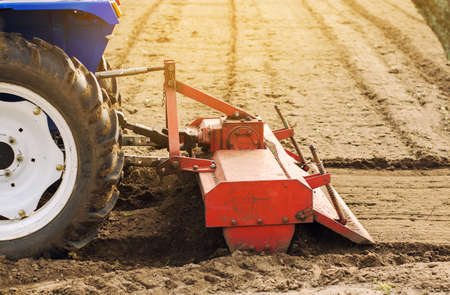 Tractor with milling machine loosens, grinds and mixes soil. Loosening the surface, cultivating the land for further planting. Farming and agriculture. Cultivates the soil. Plows a field. Archivio Fotografico