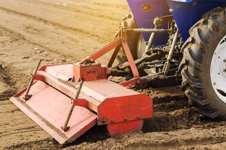 Tractor with milling machine loosens, grinds and mixes soil. Loosening the surface, cultivating the land for further planting. Farming and agriculture. Cultivates the soil. Plows a field. Archivio Fotografico - 166940557