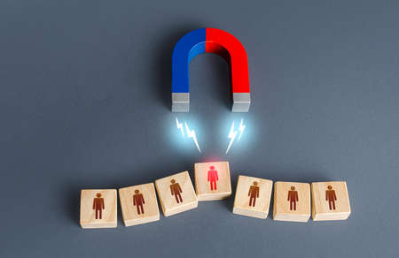 The magnet selects one person from the row. Finding the best recruiting candidate. Human resources. Search for the right person. Poaching an employee to your company. Luring. Hiring and staffing.